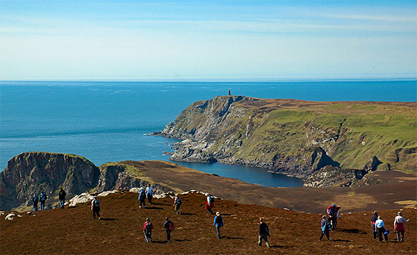 Picture of a group of walkers in a dramatic coastal landscape with steep cliffs