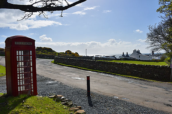 Picture of a red phone box next to a road, a distillery in the background