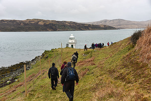 Picture of walkers approaching a small lighthouse at a sound between two islands