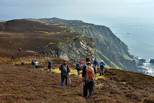 Picture of walkers walking along steep cliffs on a hazy day