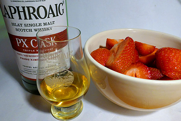 Picture of a dram and bottle of Laphroaig PX Cask Islay single malt whisky and a bowl with strawberries