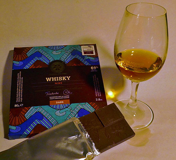 Picture of a bar of whisky chocolate nibs next to a dram of Islay single malt whisky