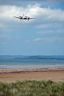 Picture of an incoming plane over a bay with a beach