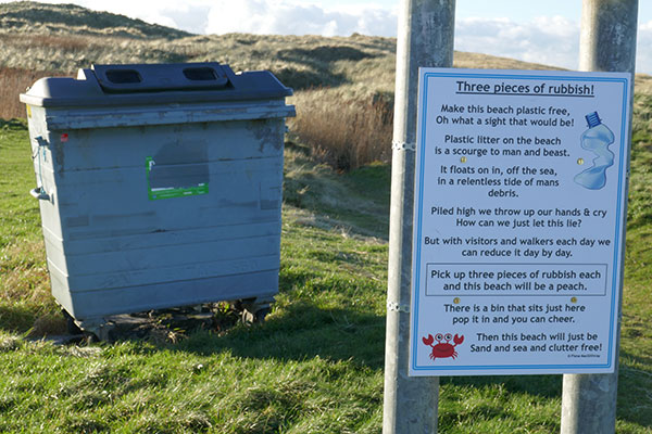 Picture of a sign encouraging visitors to pick up rubbish on a beach with a bin behind it