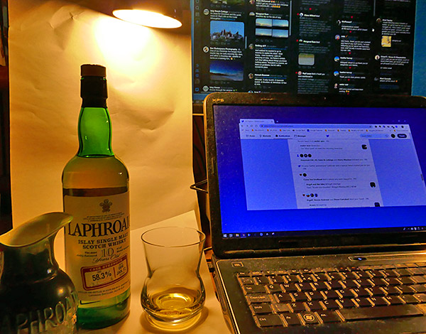 Picture of a bottle of Laphroaig 10yo CS next to a laptop showing Twitter and Tweetdeck screens