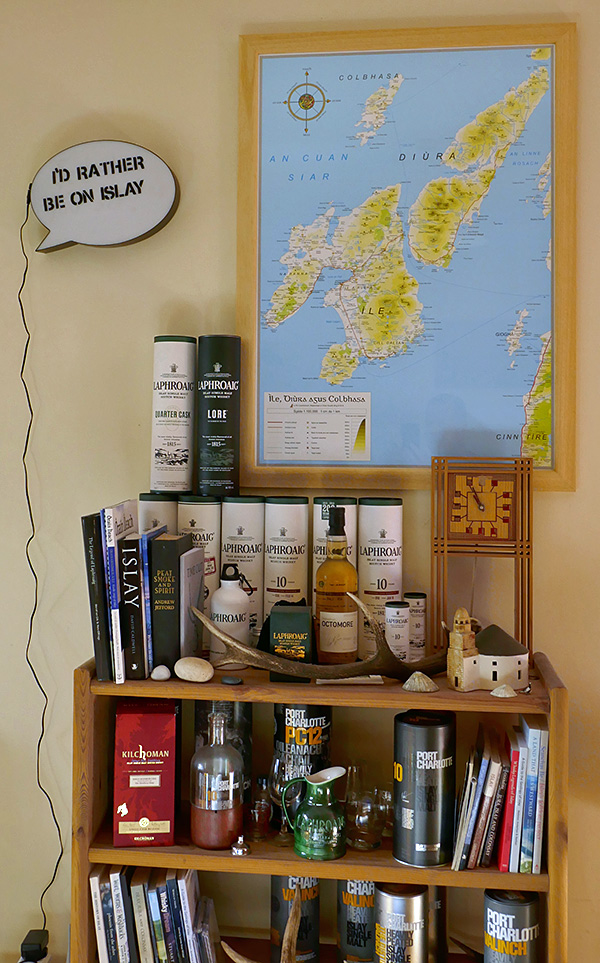Picture of a shelf with whisky and books with a map in Gaelic hanging above it
