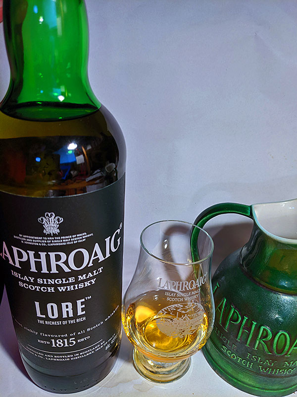 Picture of a bottle and dram of Laphroaig Lore Islay single malt whisky with a water jug