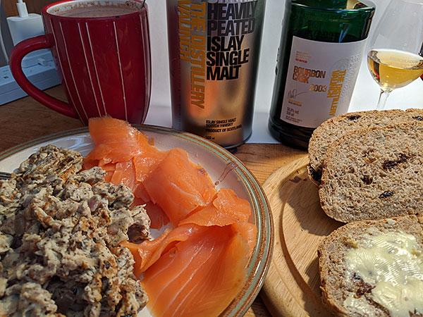 Picture of a breakfast table with scrambled eggs, salmon, fresh made bread and Port Charlotte Islay single malt whisky