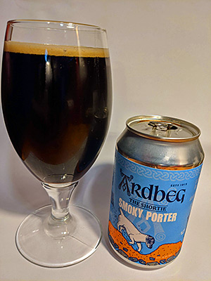 Picture of a glass of porter beer with a can of Ardbeg Smoky Porter next to it
