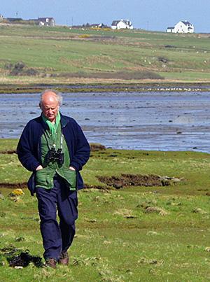 Picture of Ian Brooke walking along a loch at low tide